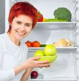 Woman against the refrigerator Stock Photography