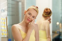 Young Woman Applies Anti Age Cream On Face Smiling. Redhead girl applying beauty cream in home bathroom at morning. Young woman taking care of her skin, looking Stock Images