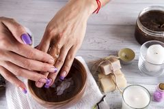 Young woman applies a coffee scrub on hands Stock Images