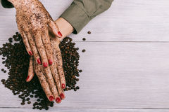Young woman applies a coffee scrub on hands Royalty Free Stock Photo