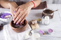 Young woman applies a coffee scrub on hands Royalty Free Stock Photos