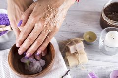 Young woman applies a coffee scrub on hands Stock Image