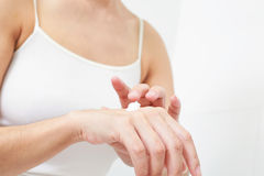 Young woman applies cream on her hands. Stock Images