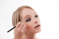 Young woman applies makeup. Close up young woman applies makeup with a soft brush beautiful skin royalty free stock image