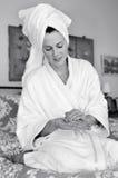 Young woman applies moisturiser to her skin Stock Photo