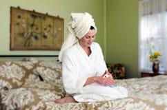 Young woman applies moisturiser to her skin Stock Photos