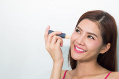 Young woman apply concealer under the eye Stock Image