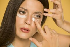 Free Young Woman Applying A Creme On Her  Low Eyelids Stock Photos - 169261603