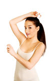 Young woman applying anti perspirant. Royalty Free Stock Photos
