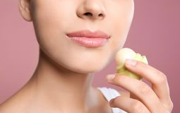 Young woman applying balm on her lips. Against color background, closeup Royalty Free Stock Images