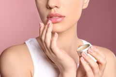 Woman applying balm on her lips against color background, closeup. Young woman applying balm on her lips against color background stock photo