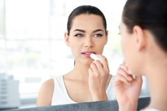 Young woman applying balm on her lips near mirror. Indoors royalty free stock image