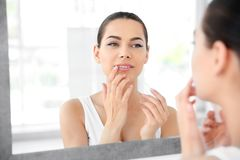Young woman applying balm on her lips near mirror. Indoors stock image