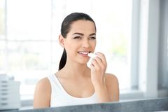Young woman applying balm on her lips near mirror. Indoors stock photo