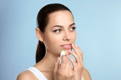 Young woman applying balm on her lips. Against color background Royalty Free Stock Photos