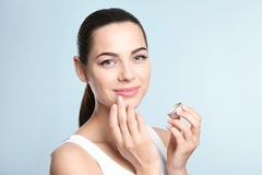 Young woman applying balm on her lips. Against color background Stock Photo