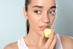 Young woman applying balm on her lips. Against color background royalty free stock image