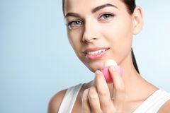 Young woman applying balm on her lips. Against color background stock image