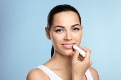 Young woman applying balm on her lips. Against color background royalty free stock photo