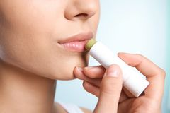 Young woman applying balm on her lips. Against color background, closeup Stock Images