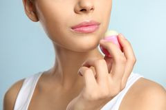 Young woman applying balm on her lips. Against color background, closeup Royalty Free Stock Photo