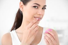 Young woman applying balm on her lips. Against light background Royalty Free Stock Photography