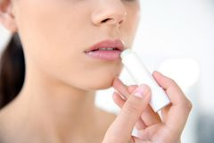 Young woman applying balm on her lips. Against light background, closeup royalty free stock image