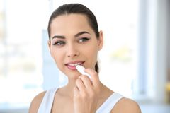 Young woman applying balm on her lips. Indoors royalty free stock images