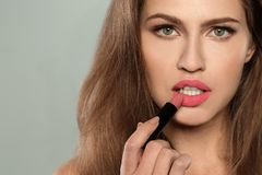 Young woman applying beautiful lipstick on gray. Space for text stock photography