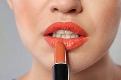Young woman applying beautiful lipstick on gray, closeup. Young woman applying beautiful lipstick on gray background, closeup royalty free stock photo