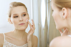 Young woman applying beauty cream, close up Stock Photo