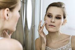 Young woman applying beauty cream, close up Royalty Free Stock Photo