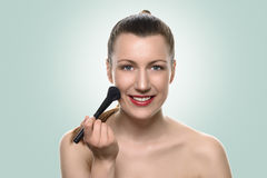 Young woman applying blush on her cheeks Royalty Free Stock Photos