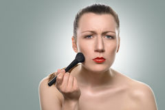 Young woman applying blush on her cheeks Royalty Free Stock Image