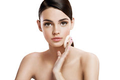 Young woman applying blusher on her face with powder puff, skin care concept Royalty Free Stock Image