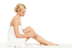 Young woman applying body cream on legs Stock Images