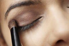 Young woman applying brown eyeshadow Royalty Free Stock Photo