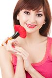 Young woman applying brush for makeup to her face Royalty Free Stock Images