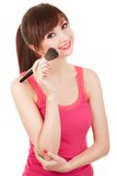 Young woman applying brush for makeup to her face Royalty Free Stock Image