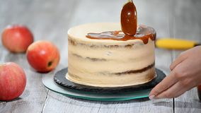 Young woman applying caramel sauce onto delicious homemade cake at table. Delicious cake with apple and whipped cream stock video footage