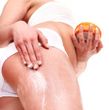 Young woman applying cosmetic cream on leg. Stock Image