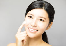 Young woman applying cosmetic cream treatment on face Royalty Free Stock Images