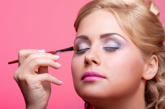 Young woman applying cosmetic paint brush Stock Photography