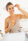 Young woman applying cosmetic serum in bathroom Stock Photo