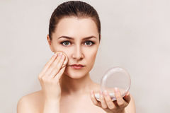 Young woman applying cosmetics powder. Royalty Free Stock Images