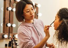Young woman applying cosmetics stock images
