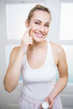 Young woman applying cream on face Stock Photo