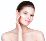 Young woman applying cream on her pretty face. Portrait of young woman applying cream on her pretty face - over white background stock image