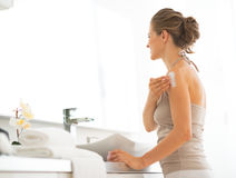 Young woman applying cream on shoulder Stock Photos