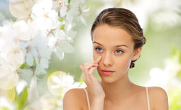 Young woman applying cream to her face Stock Photo